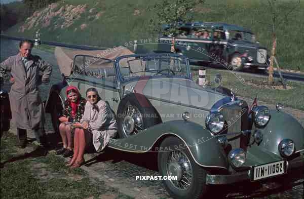 Mercedes-Benz 380 Cabriolet B, Austria 1938, with tour bus behind and family resting beside road.